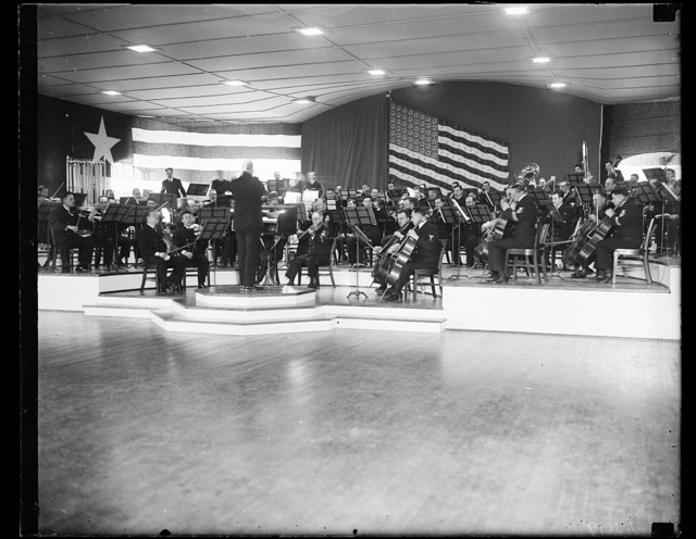 Navy band develops first symphony orchestra. This photograph shows a portion of the U.S. Navy Band's 95-piece symphony orchestra for the first time. This orchestra, under the leadership of Lt. Charles Bentor, will give its first concert at the Navy Yard Sail Loft Tuesday night (11/26/35). The Navy Band has had a small orchestra in the past which played at various functions such as White House receptions and other official social gatherings. The new and larger orchestra will give a popular music concert later in the month. 11/25/35