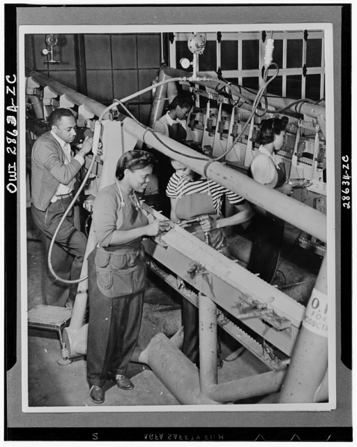 Negro men and women work side by side on the production lines at the Saint Louis, Missouri plant of the Airplane Division of the Curtiss-Wright Corporation. The male inspector in the rear checks the accuracy of the completed work of the women in the foreground