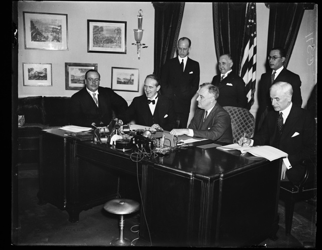 NEW BRAZILIAN TRADE PACT SIGNED. SECRETARY OF STATE CORDELL HULL, RIGHT, SIGNS THE NEW TRADE AGREEMENT BETWEEN THE UNITED STATES AND BRAZIL CALLING FOR RECIPROCAL TARIFF CONCESSIONS. THE PACT WAS SIGNED IN THE PRESIDENT'S OFFICE IN THE EXECUTIVE WING OF THE WHITE HOUSE. OTHERS IN THE PICTURE, FROM THE LEFT: BRAZILIAN MINISTER OF FINANCE ARTHUR SOUZA COSTA, BRAZILIAN AMBASSADOR OSWALDO ARANHA, AND PRESIDENT ROOSEVELT