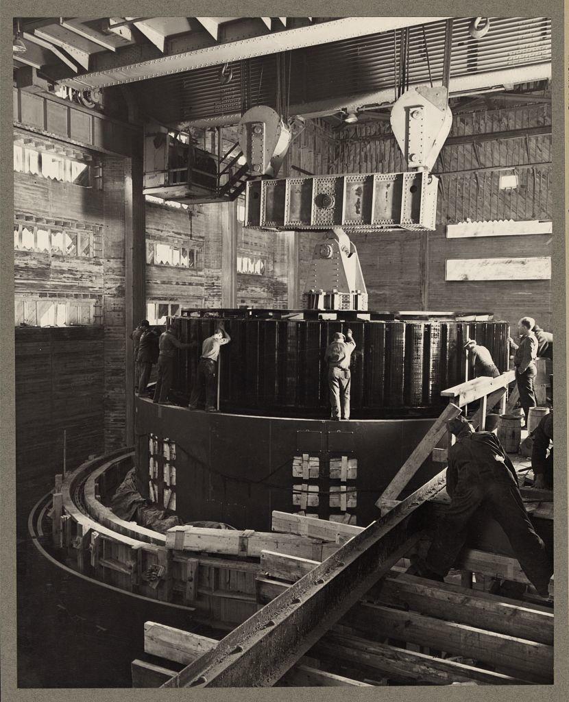 Norris Dam, Tenn. 1935-40? Workmen in the dam powerhouse installing a generator