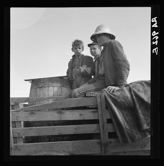On location of Resettlement Administration film near Bakersfield, California. Three brothers, drought refugees from Texas (note water barrel)