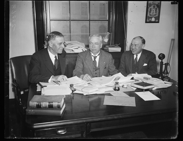 On war profits. Secretary of War Dern, left, appears before the House Military Affairs Committee to give testimony on the McSwain Take-the-Profits-Out-of-War resolution. From the left: Sec. Dern; Rep. John J. McSwain, D. of S.C., chairman, and Assistant Secretary of War Harry H. Woodring. 1/28/35