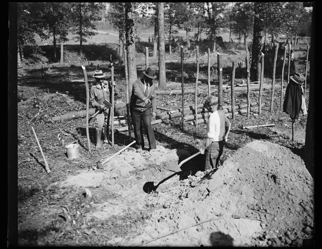 """Pilot. """"A"""" boss is shown here instructing a transient worker in ditch digging at """"Tugwelltown,"""" the government-owned project started in Maryland near the District of Columbia. 10/15/35"""