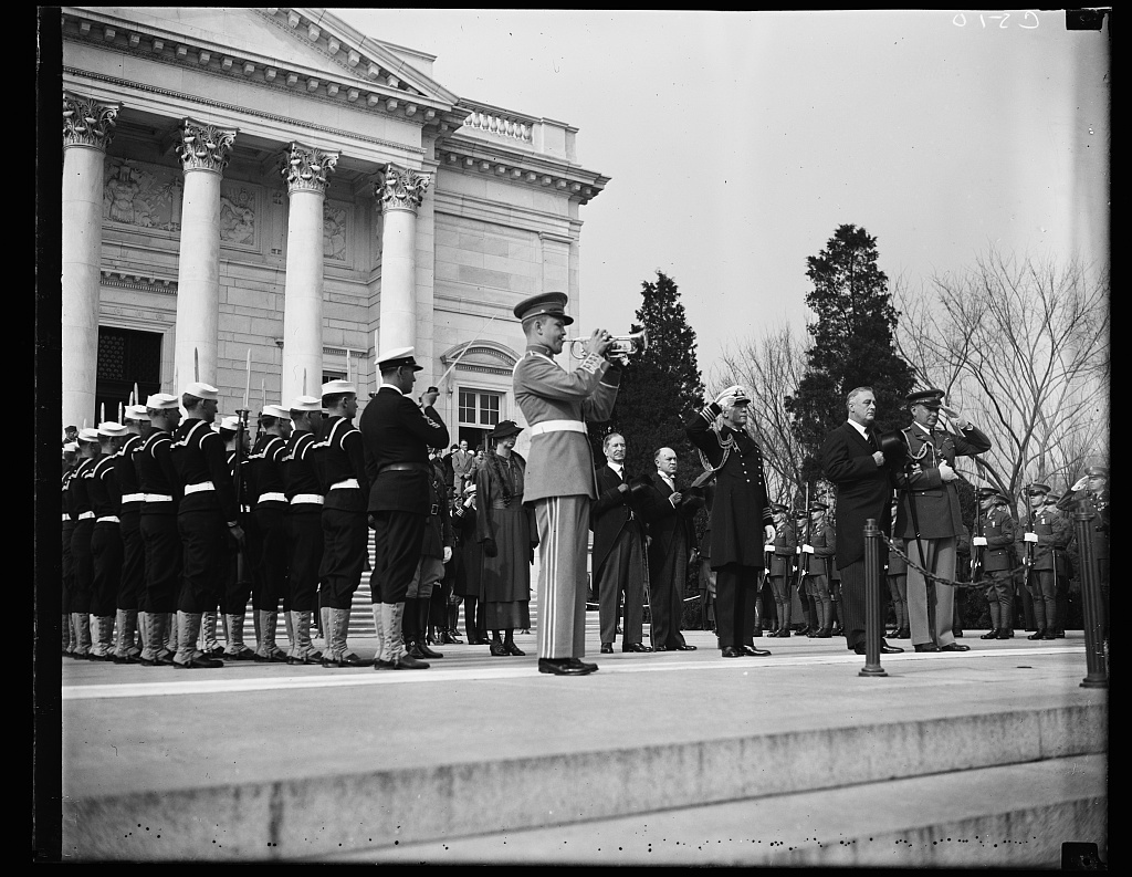 PRESIDENT AT UNKNOWN SOLDIER'S TOMB. PRESIDENT ROOSEVELT WAS THE PRINCIPAL FIGURE AT THE ARMISTICE DAY CEREMONIES AT ARLINGTON CEMETERY AND THE TOMB OF THE UNKNOWN SOLDIER. IN THE BACKGROUND CAN BE SEEN MRS. ROOSEVELT; SECRETARY OF NAVY CLAUDE SWANSON; ACTING SECRETARY OF WAR HARRY WOODRING. TO THE RIGHT IS PRESIDENT ROOSEVELT BETWEEN HIS NAVAL AIDE, CAPT. WILSON BROWN, AND HIS MILITARY AIDE, COL. WATSON
