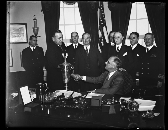 PRESIDENT AWARDS SAFE FLYING TROPHY. WASHINGTON, D.C. PRESIDENT ROOSEVELT, SEATED, AWARDS THE HERBERT SCHIFF TROPHY FOR SAFE FLYING TO LT. PHIL L. HAYNES, COMMANDER OF TRAINING SQUADRON NO. 2 AT THE NAVAL AIR STATION AT PENSACOLA, FLORIDA. T. HAYNES, LEFT, SEC. CLAUDE SWANSON, CENTER, AND SCHIFF STANDS BEHIND THE PRESIDENT