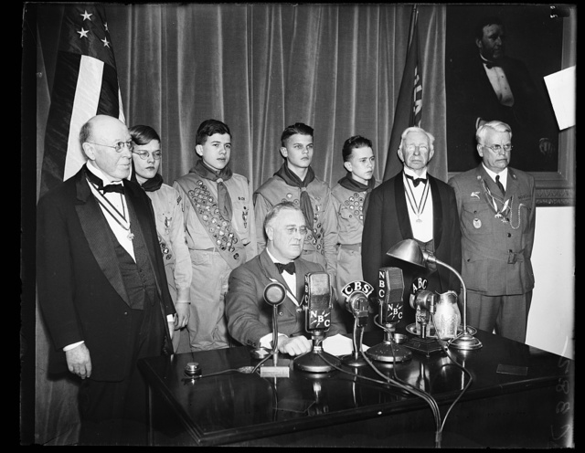 PRESIDENT CONGRATULATES BOY SCOUTS. A SHORT RADIO ADDRESS WAS GIVEN BY PRESIDENT ROOSEVELT CONGRATULATING THE BOY SCOUTS ON THE 25TH ANNIVERSARY OF THEIR FOUNDING. FROM THE LEFT: BOLTON SMITH, VICE PRESIDENT OF B.S.A.; SYDNOR HODGES TROOP 97; GEORGE KEPHART, TROOP 33; LLOYD STREET TROOP 14; PHILIP COLE, TROOP 50; COLIN H. LIVINGSTON, ORGANIZER AND PRESIDENT FOR 15 YEARS; AND JAMES E. WEST, CHIEF SCOUT EXECUTIVE