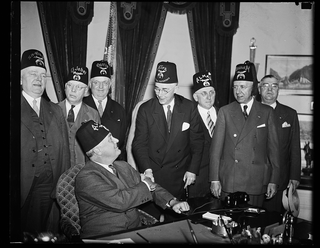 PRESIDENT GREETS SHRINE HOSPITAL HEADS. PRESIDENT ROOSEVELT, SEATED, GREETS IMPERIAL POTENTATE DANA S. WILLIAMS, OF KORA TEMPLE, IN MAINE, AND A DELEGATION OF SHRINERS REPRESENTING THE SHRINERS CRIPPLED CHILDREN'S HOSPITAL BOARD. THIS IS THE FIRST MEETING BETWEEN PRESIDENT ROOSEVELT AND SHRINERS WHO ARE HERE FOR THE NATIONAL CONVENTION BEGINNING MONDAY. FROM THE LEFT: EARLE C. MILLS, ZA-GA-ZIG TEMPLE, DES MOINES; JAMES C. BERGER, EL JEBEL TEMPLE, DENVER; WALTER S. SUGDEN ..IRIS TEMPLE, SISTERVILLE, WV; WILLIAMS; LEONARD STEUART, ALMAS TEMPLE, D.C.; CLYDE WEBSTER, MOSLEM TEMPLE, DETROIT