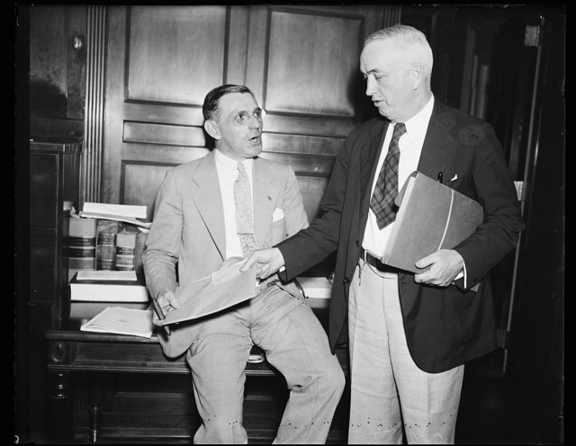 """Principals at Friday hearing [...] Rep. John J. McSwain (D. of S.C.), chairman of the House Military Com. and the key witness at the Friday hearing, Frank E. Speicher whose testimony created a sensation on """"deals"""" with the army. McSwain is standing. 7/26/35"""