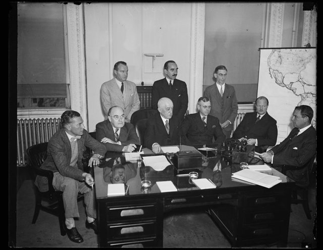 Protecting U.S. International aviation routings. This committee met in the State Department to recommend appropriate steps to protect and foster the development of American interests in the field of International aviation. The particular case in mind is the Pan-American route to the Orient. From the left, seated: Eugene Vidal, Director, Bureau of Air Commerce, Dpt. of Comm.; Stephen Gibbons, Assistant Secretary of the Treasury; R. Branch, 2nd Postmaster General in charge of Air Mail; Richard Southgate, chief of the Protocol Division, State Department; Juan T. Trippe, President of Pan-American and Witness before the group. Back row-William Miller, Bureau of Air Commerce; Rex Martin, Assistant Director of the Bureau, and Stephen Latchford, of the Treaty Division of the State Department. 10/31/35