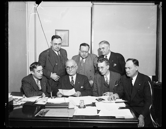 Protests textile rebels. The Emergency Committee of the United Textile Workers of American meet and file protest against textile mills refusing to obey rulings of National Textile Labor Relations board. From the left, seated: Francis J. Gorman, first Vice Pres.; Thos F. McMahon, National Pres.; James Starr, Sec-Treas.; and John A. Peel, 3rd V.P. standing, Horace A. Riviere, 4th Vice Pres.; William F. Kelly, 2nd Vice Pres.; and Joseph R. White, 5th V.P.