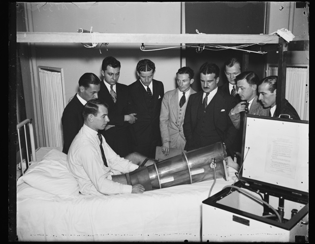 """Pumping bot examined. Students at Georgetown University Hospital gather around Chester Antos, another student, while they examine a newly devised Emerson suction pressure apparatus used to stimulate circulation in legs and feet when certain diseases threaten to neccessitate amputations. The """"boot"""", invented by Dr. Louis A. Hermann of Cincinnati, induces circulation by alternately increasing and decreasing air pressure. It is considered a consequential physiological development by doctors who examined it here, 11/12/35"""