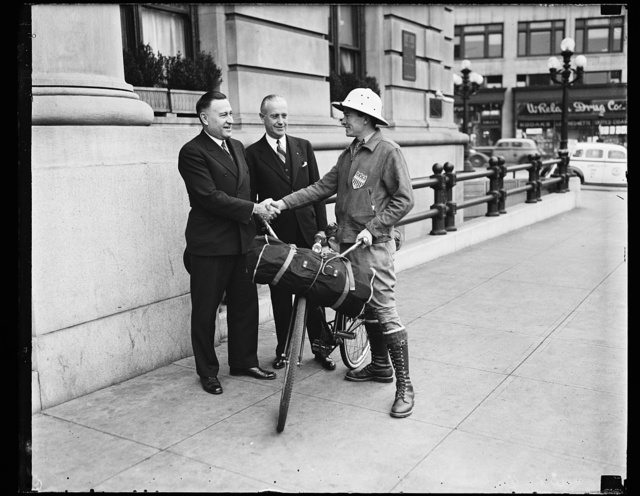 Ready for international bicycle ride. Wash. D.C. Henry G. Slaughter of Washington, supported by those interested in publicizing the Inter- American highway, prepares to leave Washington for a trip which will carry him, if he is successful, down into the tropics through Central American to the Argentine. From the left: Charles M. Upham, Engineer and Director of the American Road Builders Ass'n., H.F. Summerville, Managing Director of the Willard Hotel, and Slaughter, 11/23/35