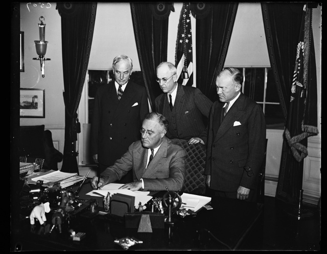 ROOSEVELT SIGNS PHILIPPINE COMMONWEALTH PROCLAMATION. PRESIDENT ROOSEVELT SIGNS THE PROCLAMATION TERMINATING THE EXISTING GOVERNMENT OF THE PHILIPPINES AND ESTABLISHING THE COMMONWEALTH UNDER A CONSTITUTIONAL FORM OF GOVERNMENT. HE ALSO WISHED THE PHILIPPINO PEOPLE GOOD LUCK. FROM THE LEFT: SECRETARY CORDELL HULL, GEN. MALIN CRAIG, CHIEF OF STAFF, AND ACTING SECRETARY OF WAR HARRY WOODRING. SECRETARY GEORGE DERN IS IN THE PHILIPPINES AT THIS TIME