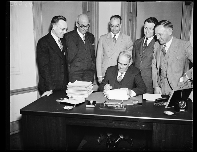 Rural electrification program speeded. Executives of the Rural Electrification Administration gather around their chief, Morris L. Cooke, as seven projects are launched to give 4,000 farm homes electric light. Cooke is seated. From the left, standing: Melvin O. Swanson, Chief Engineer; W.E. Herring, Special Assistant to the Administrator; L.A. Sears, Chief of Projects Section Guy Thaxon, Engineer, and Charles W. Bass, Assistant Chief Engineer, 11/4/35