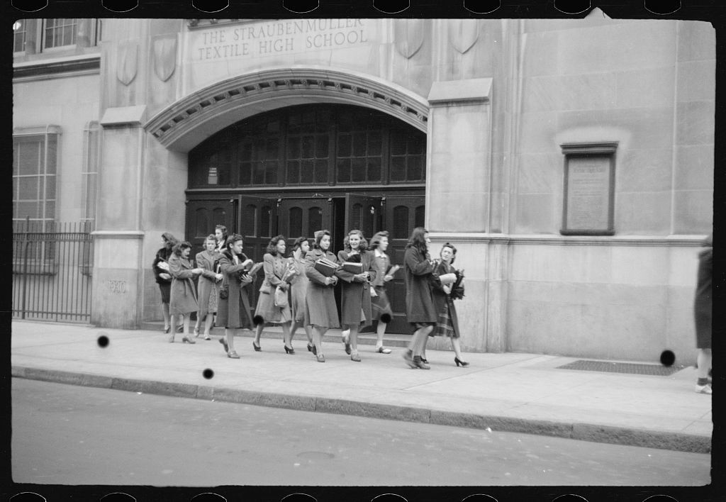 [Schoolgirls walking along street in front of Straubenmuller Textile High School, New York, New York]