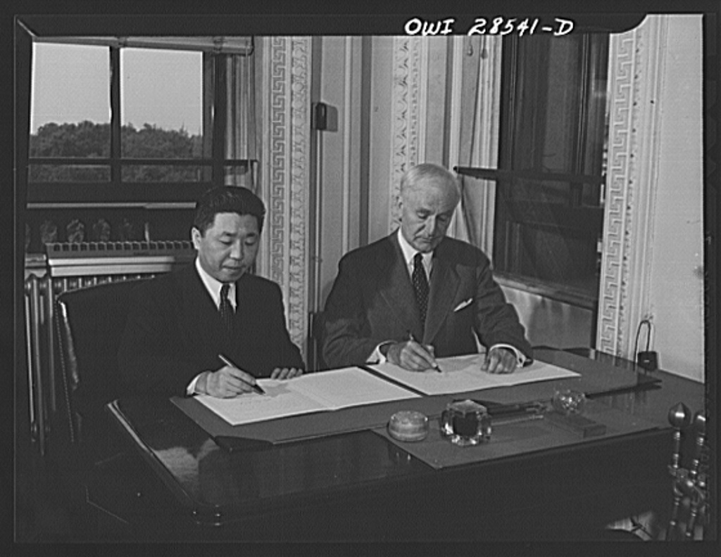 """Secretary of State Cordell Hull and Chinese Ambassador Wei Tao-Ming at the State Department exchanging ratifications of the treaty abolishing extra-territorial """"rights"""" of the United States in China.  The treaty provided that it becomes effective at the time of this exchange"""