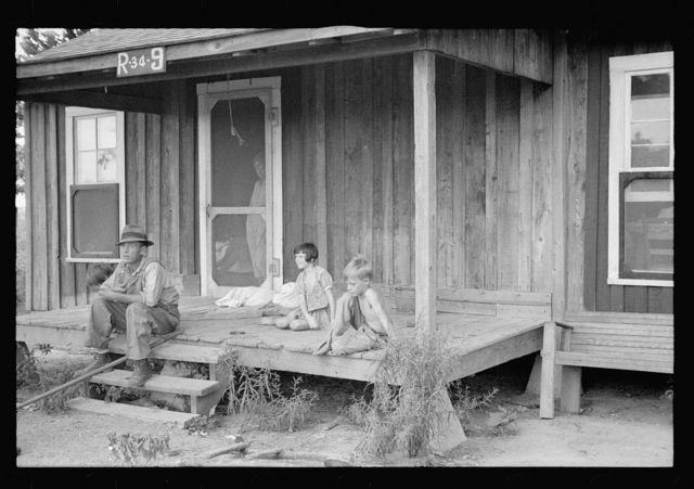 Sharecropper and children in front of company house. Wilson cotton plantation, Mississippi County, Arkansas