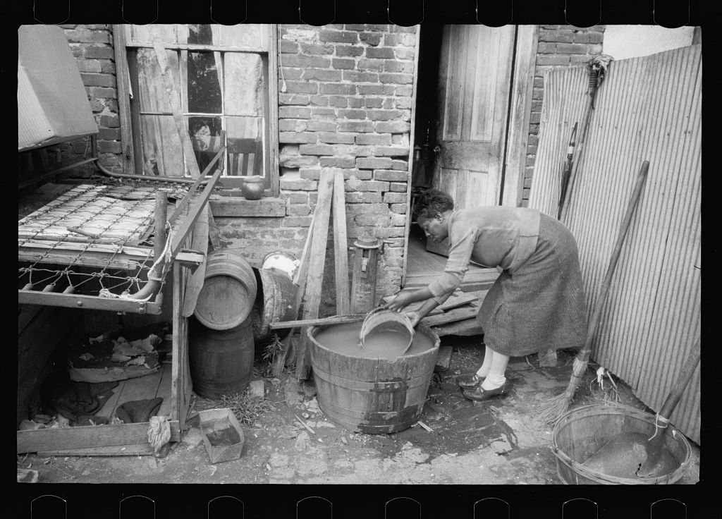 Slum backyard water supply, Washington, D.C. Backyard typical to a group of houses very close to the House office building, showing only available water supply