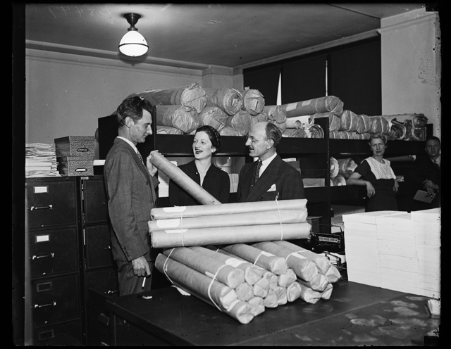Slum clearance plans rushed projects. The Housing Division of [RWA?] begins shipment of 3,300 sets of plans and 9,900 sets of specifications covering 46 slum clearance projects in widely separated sections of the country. About 25,000 modern homes are program. From the left: C.W. Fitch, assistant director of the Housing division, [...]athleen Brown, a clerk, and A.R. Clas, [Director?] /21/35