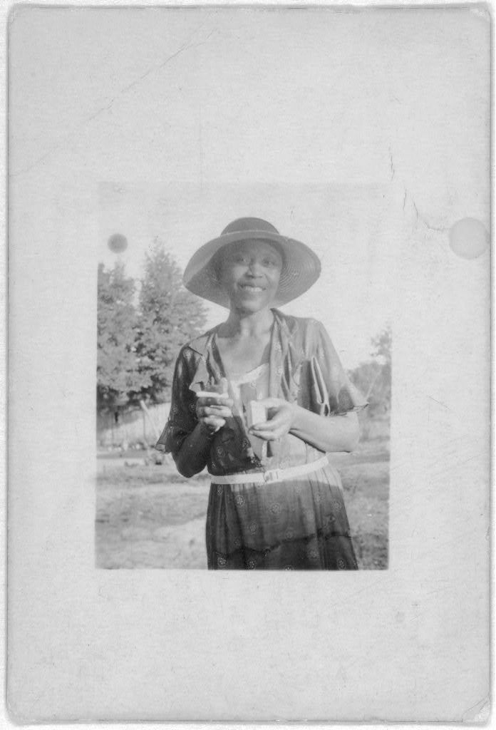 [Smiling woman, three-quarter-length portrait of unidentified person standing outdoors]