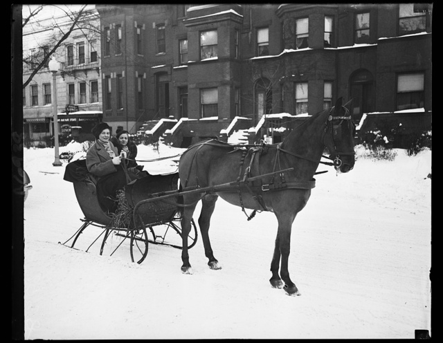 Socialites enjoy winter. These two prominent members of Washington's social set enjoy the clear, cold aftermath of the blizzard which left the streets covered with nearly a foot of snow. Miss Evelyn Walker, daughter of Mr. and Mrs. Harold Walker, is wearing the Russian-type hat. Her companion is Mrs. Eppes Hawes Preston, daughter of Former Senator and Mrs. Harry B. Hawes