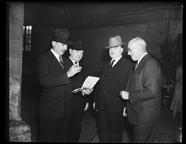 """Still in disagreement. This executive photograph taken at the coal strike conference in Washington found the principles as far apart as the poles. From the left: Edward F. McGrady, Assistant Secretary of Labor; James F. Dewey, Labor Department conciliator; John L. Lewis, President of United Mine Workers, and M. L. Garvey, Coal Operator of New Riverfield, W.Va. Mr. Lewis said several plans of compromise had been under discussion but that nine cents a tone was the last work from him, """"take it or leave it."""" McGrady told newsmen that FERA Hopkins had assured relief to striking miners when it became necessary, 9/24/35"""