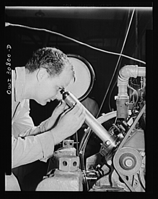 Substitute fuels tested. Emmet L. Reed, laboratory assistant at the U.S. Bureau of Standards, uses a special microscope to measure the degree of wear which substitute gasoline has produced on an automobile engine cylinder