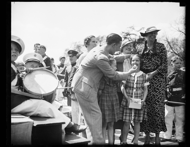 SURPRISED? MAGICIAN CHRISTOPHER, LEFT, EXTRACTS AN EGG, SO IT SEEMS, FROM THE MOUTH OF SURPRISED DIANA ROOSEVELT, DAUGHTER OF MRS. J. HALL ROOSEVELT OF DETROIT, AT THE ANNUAL EASTER EGG ROLLING AT THE WHITE HOUSE. MRS. FRANKLIN ROOSEVELT IS SHOWN AS SHE GREETED THE THOUSANDS OF WASHINGTON YOUNGSTERS