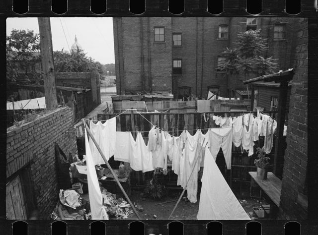 The Capitol can be seen in the background of this backyard slum scene, Washington, D.C.