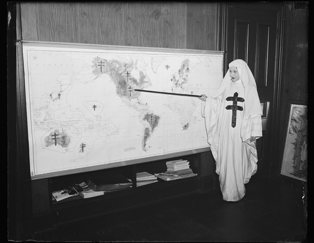 """Tuberculosis battle map, Wash. D.C. Miss Mildred Showalter of Washington, dressed as the Spirit of the Double-barred cross of the anti- tuberculosis movement throughout the world, points to various battlefronts throughout the world where the fight is being carried on against the """"White Plague."""" On Nov. 26, ambassadors from various countries will give radio reports on progress of their countries and officially launch this [...] campaign in the United States, 11/25/35"""