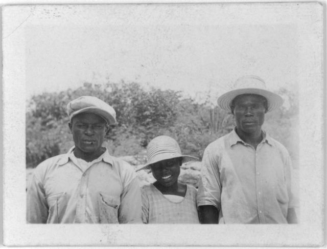 [Two men and a girl posed standing in foreground, possibly from the visit by Alan Lomax and Mary Elizabeth Barnicle to Andros Island in the Bahamas]