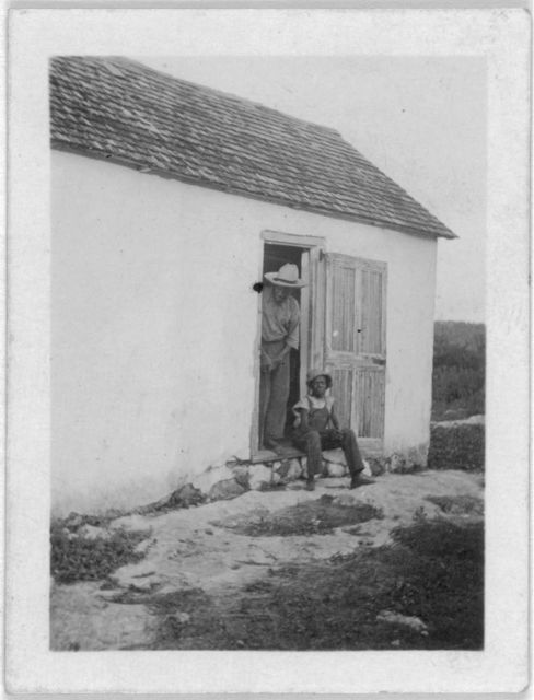 [Two men in doorway, one sitting, one standing, possibly from the visit by Alan Lomax and Mary Elizabeth Barnicle to Andros Island in the Bahamas]