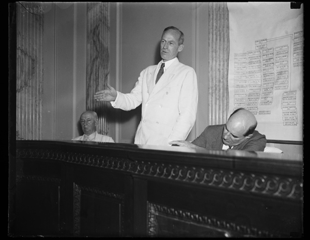 """Tydings said he didn't. Sen. Millard E. Tydings, D. of Md., standing, injected himself into the Senate lobby investigating committee where he questioned B.B. Robinson, the utility lobbyist, concerning the statement made by Robinson that he, Tydings, had attended a cocktail party. Sen. Tydings said he didn't attend. Robinson said Tydings was invited. And the Senator ended the discussion by saying to Robinson, """"Hereafter when you use my name in this testimony you be damned sure you are right."""" [...] is in the picture but taking no part in the discussion, 8/23/35"""