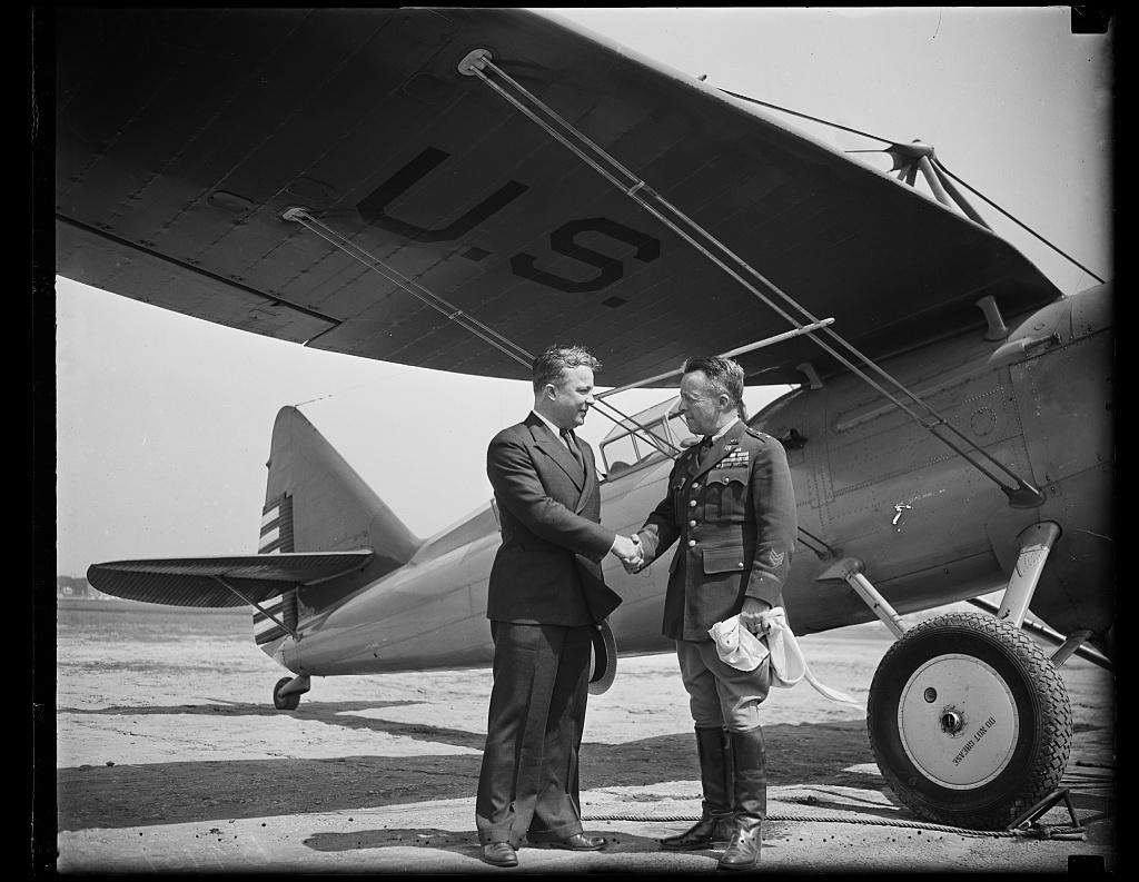[Unidentified men shaking hands at U.S. airplane]