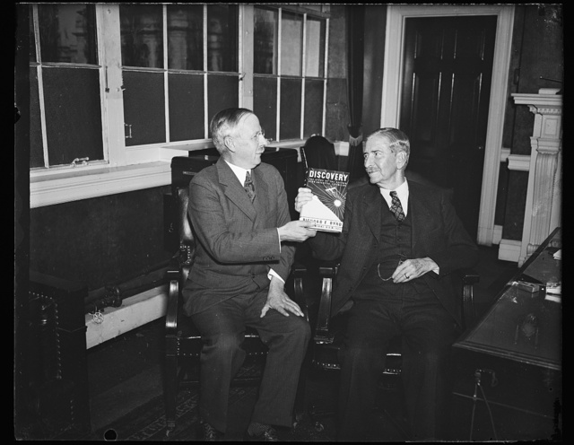 """Wash. D.C. First bird book., Dr. Gilbert Grosvenor, President of the National Geographic Society, left, presents to Secretary Claude A. Swanson a special copy of """"Discovery"""" by Rear Admiral Richard E. Byrd, writing of his second South Polar expedition. 11/22/35"""