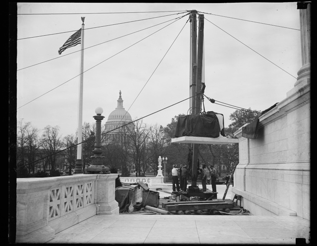 "Wash. D.C. Ready for lift. This photograph shows the statue as it is made ready for the ""ride up"" to the place where it will rest beside the entrance to the new U.S. Supreme Court building. The Capitol dome is in the background. 11/6/35"
