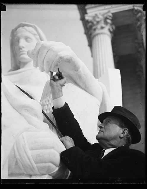 """Wash. D.C. Sculptor finishes task., J.E. Frasier, of New York, sculptor, puts the final touches and the official okay on """"Contemplation of Justice,"""" one of two statues of his in front of the new U.S. Supreme Court. Working under him as carvers are Gino A. Ratti and E. Jatti, father and son. 11/22/35"""
