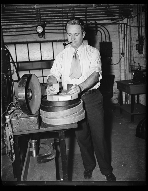 Wash. D.C. Standards Bureau brake test. Richard S. Dill of the U.S. Bureau of Standards is examining a portion of brake lining after being subjected to a test and comparing it with a new piece. 10/4/35