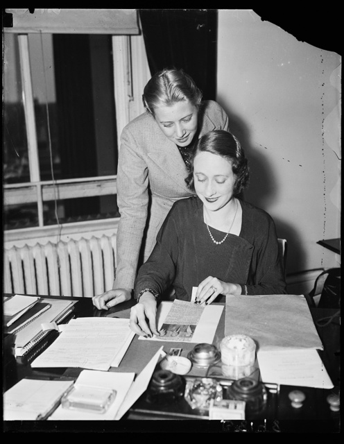 """Wash. D.C. Working on housing survey figures. Miss Fritzi Honick, left, and Helen Hasting, Secretary to Peter Grimm, who is making a housing survey, are compiling data which shows a surplus of less than 4 percent in housing """"East"""" of the Mississippi. A plan is being worked out in the Treasury Department to prevent a vertical rise in rents. 10/29/35"""