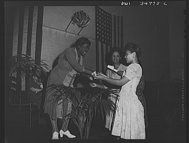 Washington, D.C. Mrs. Mary McLeod Bethune, President of the National Council of Negro women, presenting certificates to hostesses for USO duty, at the Phyllis Wheatley YWCA on Rhode Island Avenue. Facing the camera is Miss Dorothy Height, Director of the YWCA