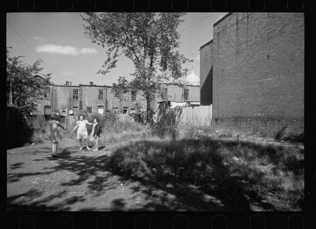 White girls playing in slum section near Capitol inhabited mostly by Negroes. Note Capitol dome in right background. Washington, D.C.