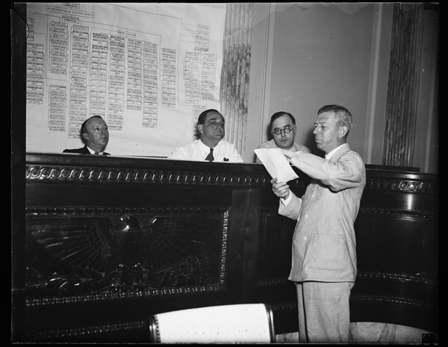 William A. Hill, Boston, Attorney for Howard C. Hopson, utility emperor, appears before the Senate Lobby Investigating Committee in the morning. In the afternoon the committee asked for a contempt citation for Hill, after the committee had asked for a similar citation for Hopson. In this picture, from the left, are Sen. Hugh Black, D. of Ala., chairman, Sen. Sherman Minston, D. of Ind., and Sen. Lewis B. Schwellenbach, D. of Wash., and Hill, 8/14/35