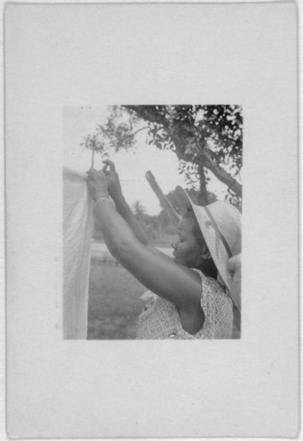 [Woman hanging laundry on the line, Eatonville, Fla., taken during the Lomax, Hurston, Barnicle 1935 expedition to Georgia, Florida and the Bahamas]