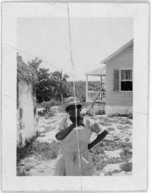 [Woman standing, facing front, two houses in background, possibly from the visit by Alan Lomax and Mary Elizabeth Barnicle to Andros Island in the Bahamas]