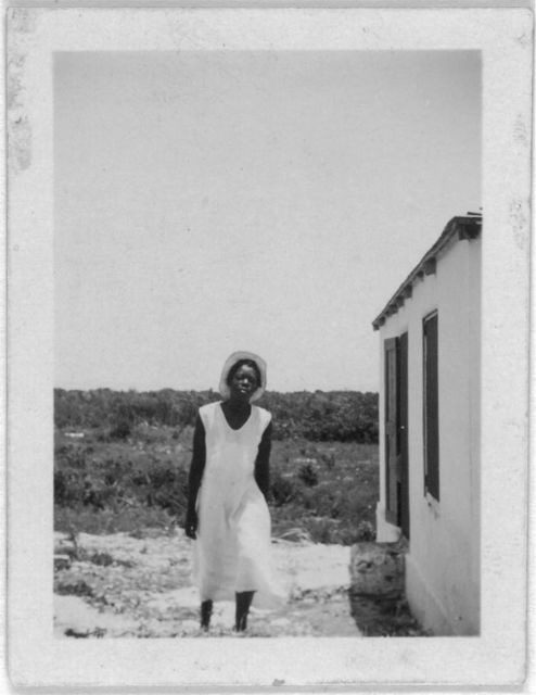[Woman standing outside house, possibly from the visit by Alan Lomax and Mary Elizabeth Barnicle to Andros Island in the Bahamas]