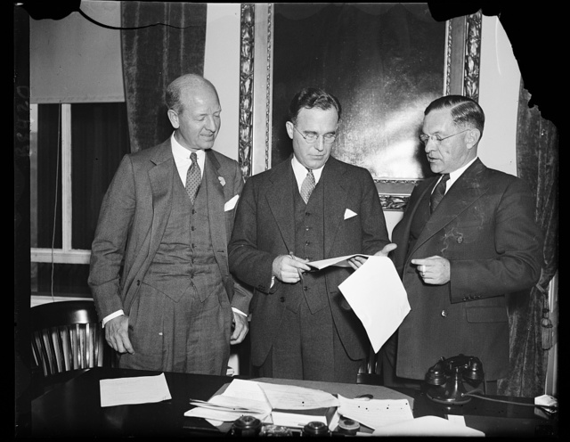 Working on housing display. These representatives of the Manufacturers' Housing Display Council and the Treasury Department discuss methods of stimulating building to care for a shortage of houses indicated in a recent survey. From the left: Peter Grimm, assistant to the Secretary of the Treasury; Russell G. Creviston, chairman of the council, and Marshall Adams, Vice Chairman. Creviston is a Crane Co., official, and Adams is with American Radiator Co. Grimm is President of William A White & Sons of New York, who has been loaned to the Treasury Department, 10/30/35