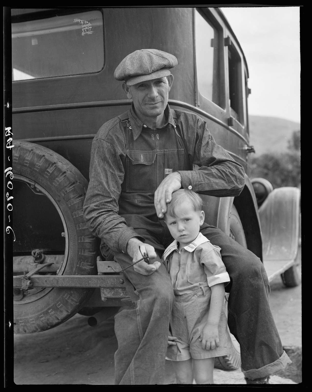 1936 drought refugee from Polk, Missouri. Awaiting the opening of orange picking season at Porterville, California