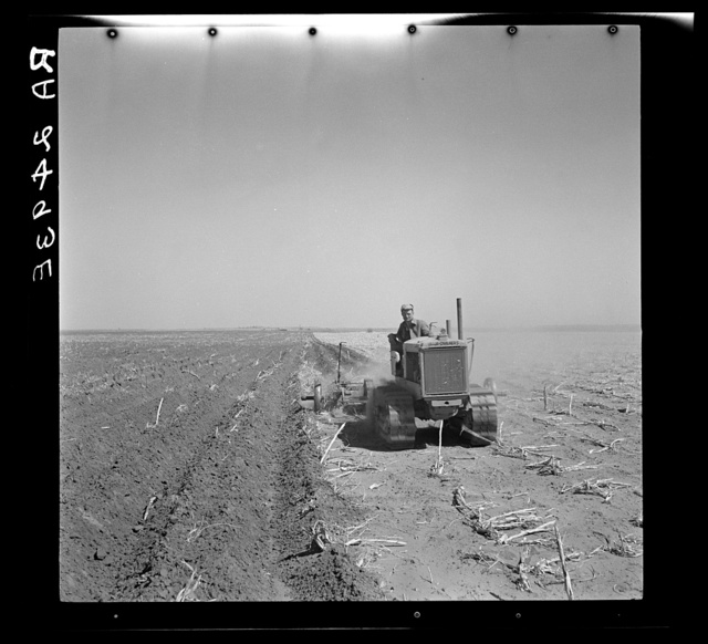 A farmer listing his fields under the wind erosion control program. He receives twenty cents an acre for the work. Liberal, Kansas
