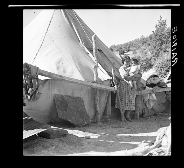 An Indian woman in front of her tepee. Many Indians on the Mescalero Reservation in New Mexico live in such primitive tents