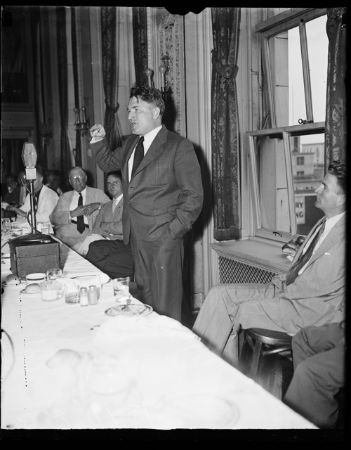 "Blasts New Deal, Washington, D.C., August 7. Photo shows one of the chief speakers of the old Huey Long movement as he addressed the members of the press at the pre club in Washington. He blasted the ""New Deal"" in no uncertain terms. Photo shows the Rev. Gerald L.K. Smith in action front of the news"